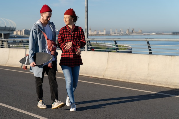 Young casual couple of hipsters walk city road carry longboard talk over urban skyline background