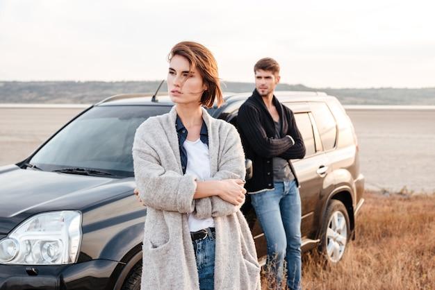 Молодая пара случайных, стоя у своей машины на берегу моря