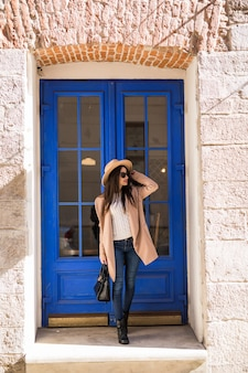Young casual dressed lady in bright coat hat and sunglasses is standing in front of blue door