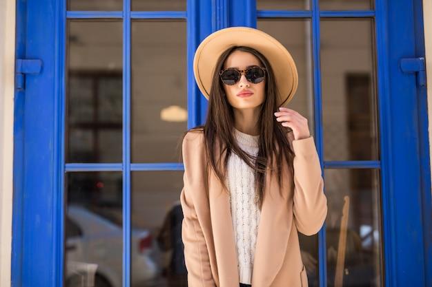 明るいコートの帽子とサングラスの若いカジュアルな服を着た女性は青いドアの前に立っています。