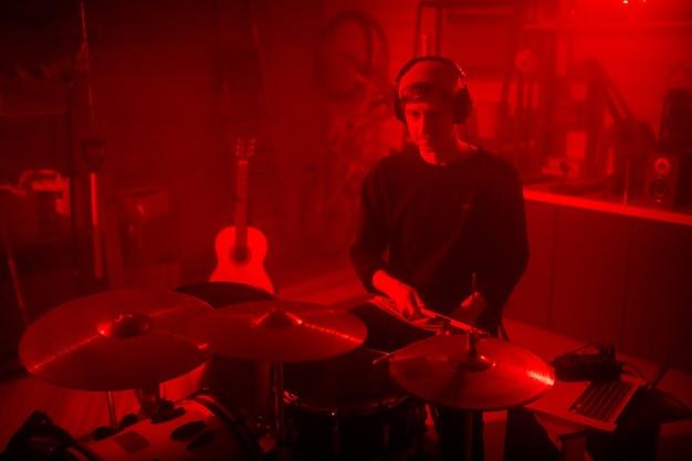 현대적인 스튜디오 또는 차고에서 drumset으로 새로운 물건을 녹음하는 동안 헤드폰으로 음악을 듣는 젊은 캐주얼 드러머