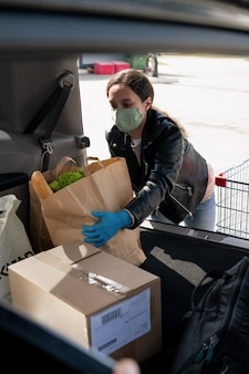 Young casual female in protective mask and gloves putting paperbags