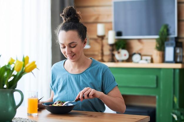 Молодая непринужденная женщина сидит за обеденным столом на кухне, ест спагетти и пьет фруктовый сок