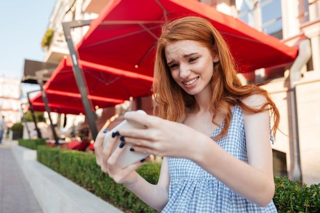 携帯電話でゲームをプレイするカジュアルな少女