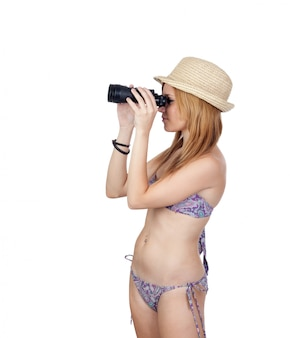 Young casual girl with bikini watching for a binocular solated on white background