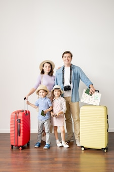 手荷物を持つ若いカジュアルな夫と妻、旅行前にスタジオで壁に立っている幼い息子と娘