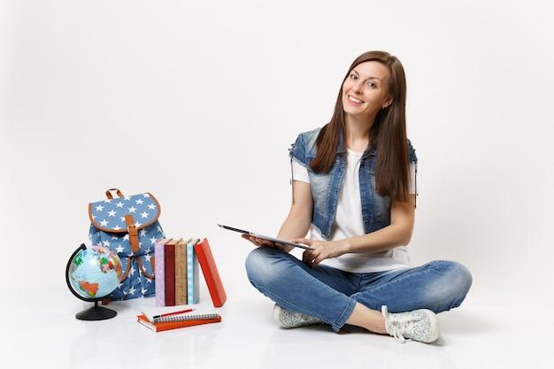 Giovane studentessa casual gioiosa in abiti di jeans che tiene in mano un computer tablet pc seduto vicino al globo, libri di scuola zaino isolati