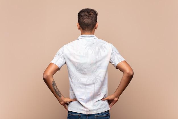 若いカジュアルな男の背面または背面図