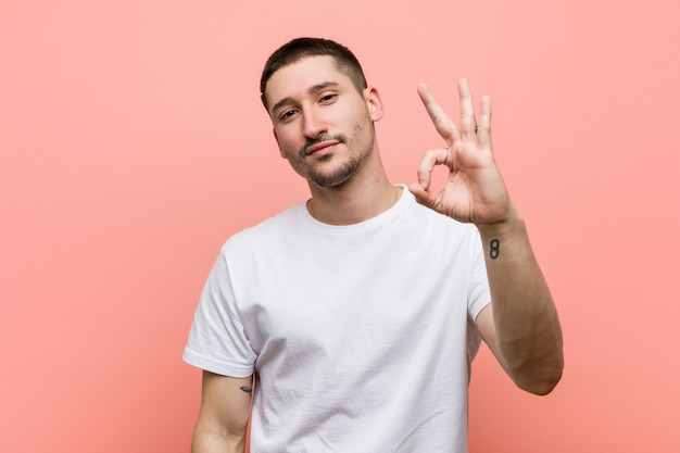 Young casual man cheerful and confident showing ok gesture.