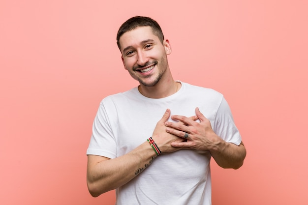 Young casual man has friendly expression, pressing palm to chest