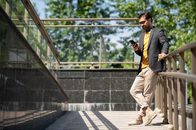 Молодой случайный мужчина в бежевых джинсах, желтом пуловере и темно-синем пиджаке прокручивает смартфон у перил на открытом воздухе