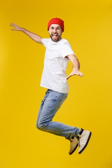 Young casual man jumping for joy on yellow gold
