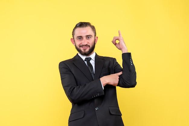 自己満足の表情で指を上向きの若いカジュアルな男