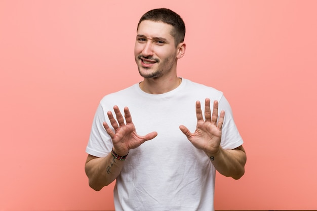 Young casual man rejecting someone showing a gesture of disgust.