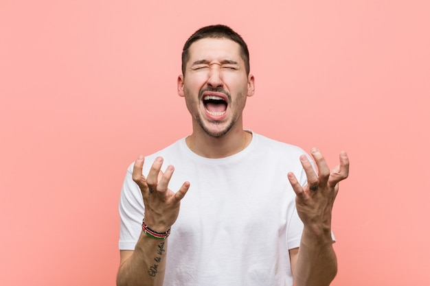 Young casual man screaming with rage.