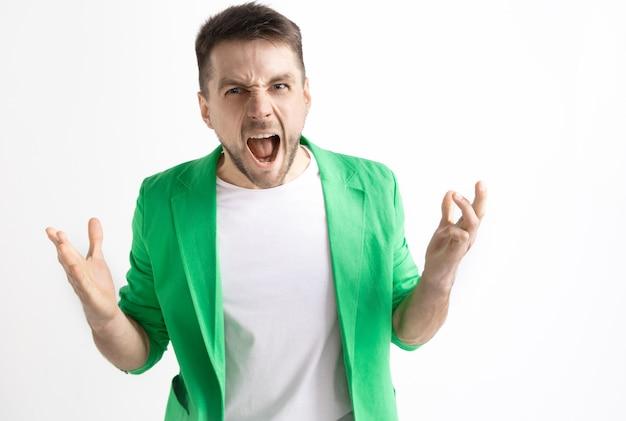 若いカジュアルな男が叫んでいます。叫ぶ。スタジオの背景で叫んで泣いている感情的な男。男性の半身像。人間の感情、表情の概念。