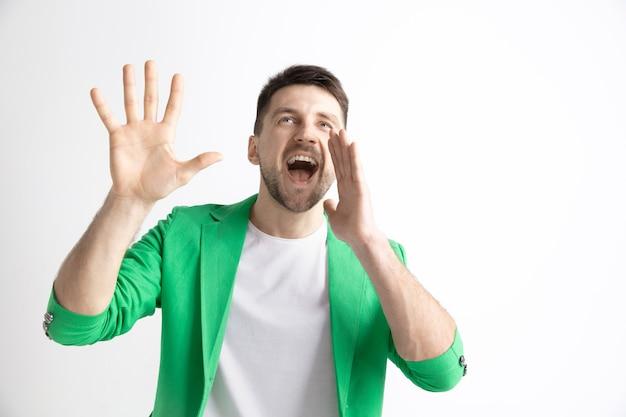 若いカジュアルな男が叫んでいます。叫ぶ。スタジオの背景で叫んで泣いている感情的な男。男性の半分の長さの肖像画。人間の感情、顔の表情の概念。