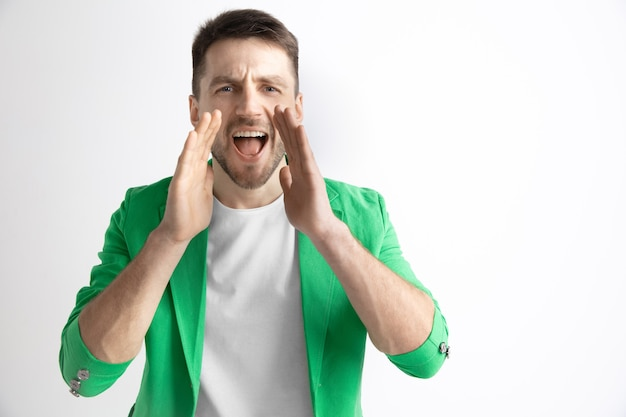 Young casual man shouting. shout. crying emotional man screaming on studio background. male half-length portrait. human emotions, facial expression concept.