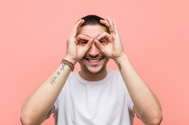 Young casual man showing okay sign over eyes