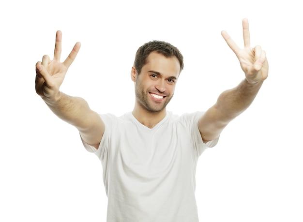 ポケットに手を入れてカメラに向かって微笑んで勝利のジェスチャーを示す若いカジュアルな男。白い背景で隔離