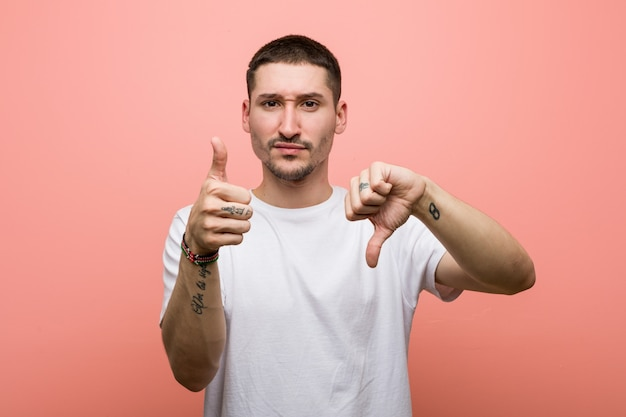 Young casual man showing thumbs up and thumbs down, difficult choose concept