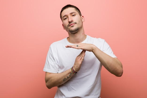 Young casual man showing a timeout gesture.