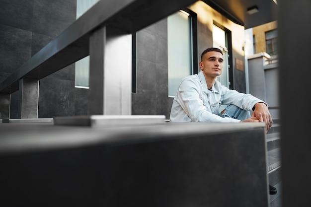 通りで一人で階段に座っている若いカジュアルな男