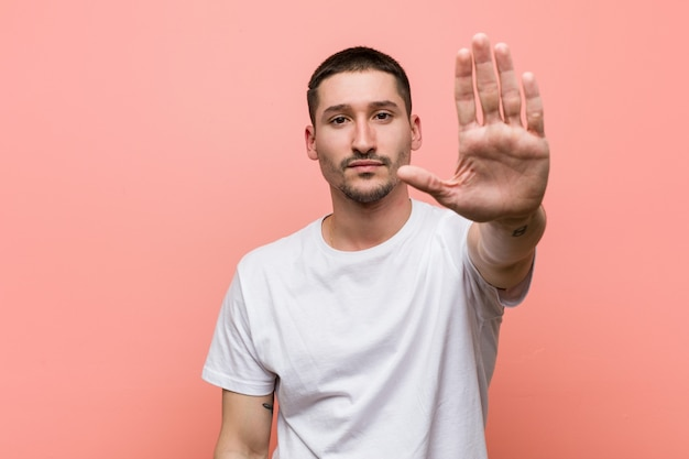 Young casual man standing with outstretched hand showing stop sign, preventing you
