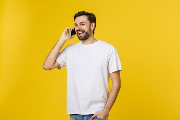 Young casual man talking on the phone isolated