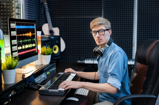Young casual man with headphones looking at you while sitting by workplace in recording studio in front of computer screen