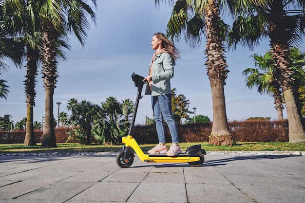 Young casual modern active millennial woman using electric scooter for fast mobile riding through the city