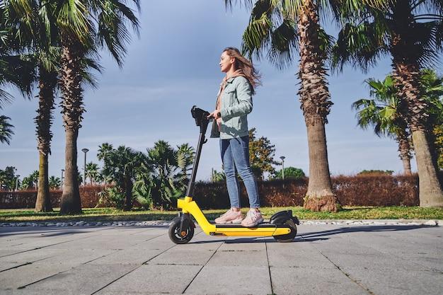 Молодая повседневная современная активная женщина-миллениал использует электросамокат для быстрой мобильной езды по городу