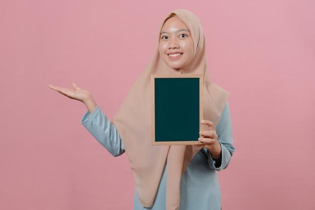 緑のボードを保持し、ピンクの背景にコピースペースを示す若いカジュアルなイスラム教徒の女性