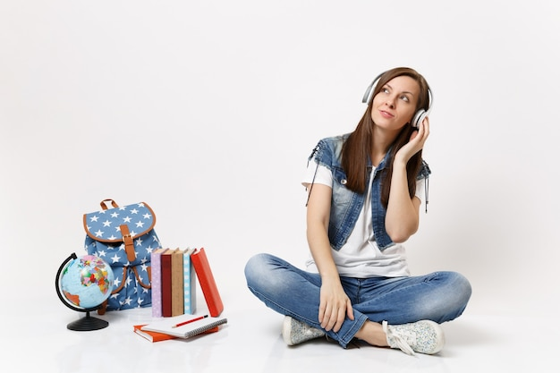 Young casual pensive concerned woman student with headphones listening music sitting near globe backpack school books isolated