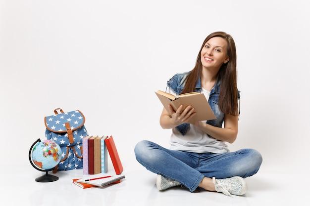 Giovane studentessa casual piacevole in abiti di jeans che tiene la lettura di libri seduta vicino al globo, zaino, libri di scuola isolati