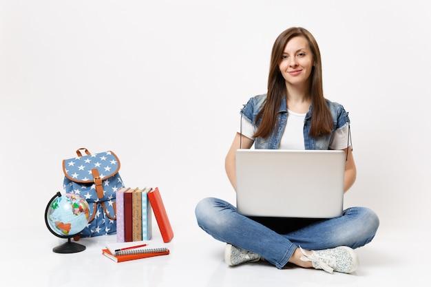 Молодой случайный довольно улыбающийся студент женщина, держащая с помощью портативного компьютера, сидя рядом с земным шаром, рюкзаком, школьными учебниками