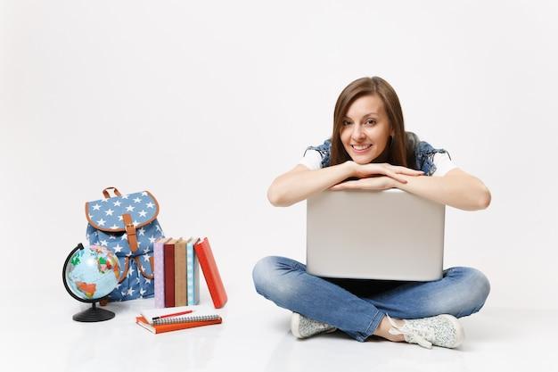 Молодая случайная симпатичная улыбающаяся студентка, опирающаяся на портативный компьютер и сидящая возле рюкзака с глобусом, изолированные школьные учебники