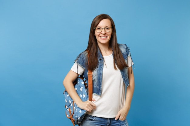 白いtシャツ、青い背景で隔離のポケットに手を入れて眼鏡をかけてバックパックとデニムの服を着た若いカジュアルなスマート女性の学生。高校大学カレッジコンセプトの教育。