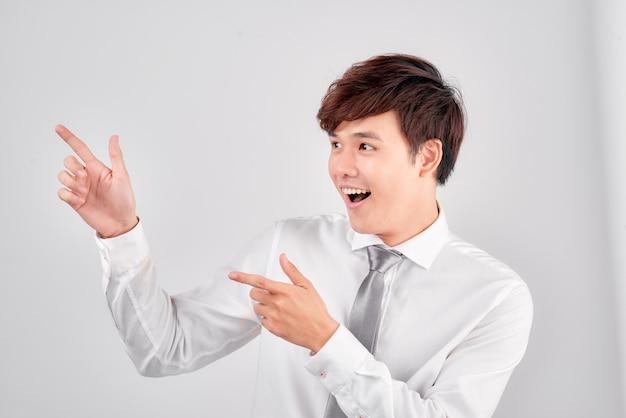 若いカジュアルな学生は白い背景の上の指を指します