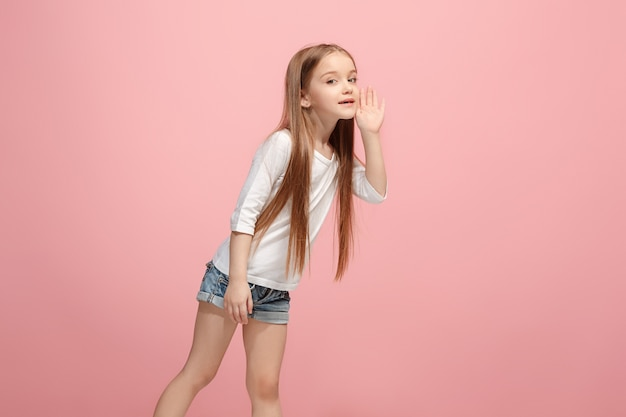 Giovane ragazza teenager casuale che grida isolato in rosa