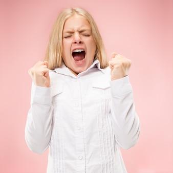 Giovane ragazza teenager casuale che grida. grido. adolescente emotivo piangente che grida sullo spazio rosa. ritratto femminile a mezzo busto