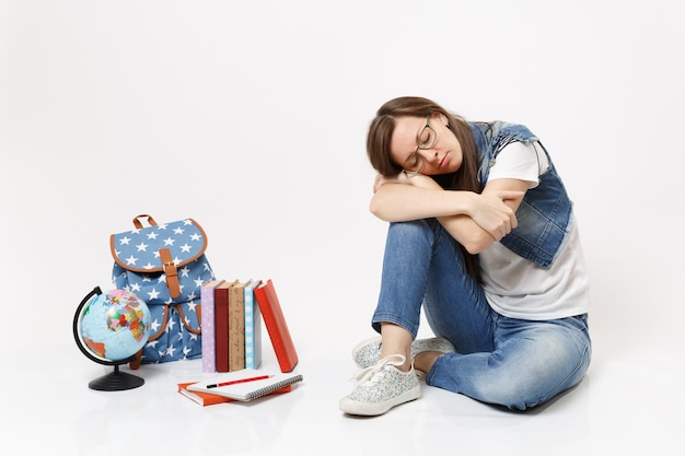 Young casual tired relaxed woman student in denim clothes glasses sleeping sitting near globe, backpack, school books isolated