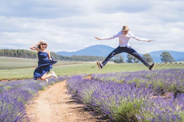 ラベンダー畑でジャンプする若いカジュアルなトレンディな男の子と女の子。青い雲の夏の昼間。