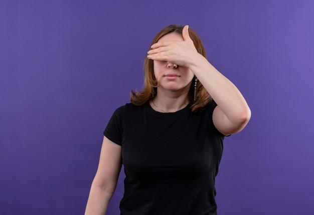 コピースペースと孤立した紫色の壁に手で目を閉じる若いカジュアルな女性