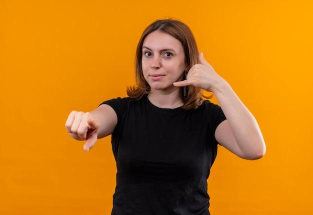 呼び出しジェスチャーをし、孤立したオレンジ色の壁を指して見ている若いカジュアルな女性