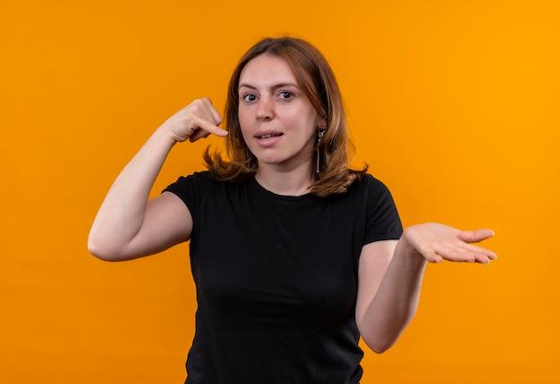 呼び出しジェスチャーをし、孤立したオレンジ色の壁に空の手を示す若いカジュアルな女性