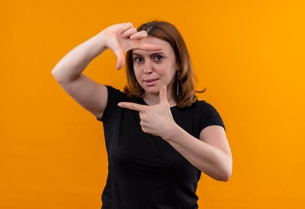 コピースペースと孤立したオレンジ色の壁にフレームを身振りで示す若いカジュアルな女性