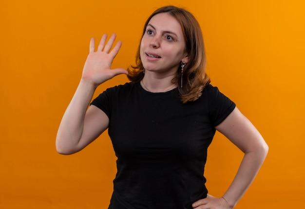 Giovane donna casuale che gesturing ciao e che esamina il lato sinistro con la mano sulla vita sulla parete arancione isolata