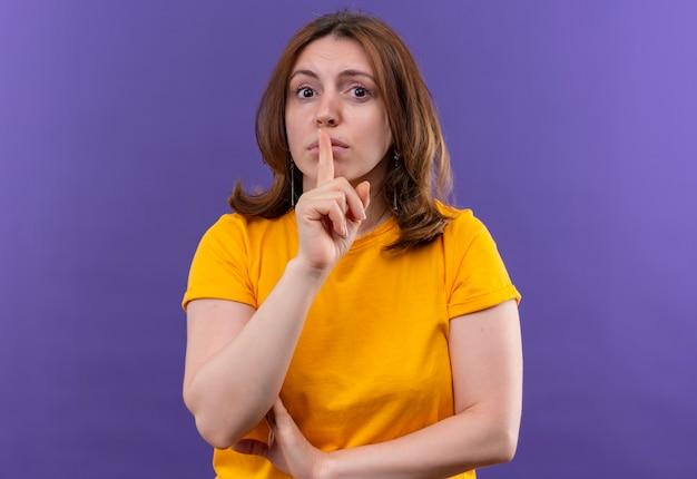 コピースペースと孤立した紫色の壁に口に指でsileceを身振りで示す若いカジュアルな女性