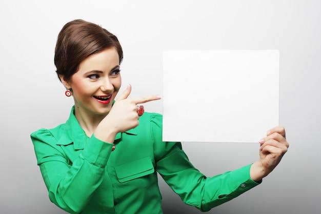 空白記号を保持している幸せな若いカジュアルな女性
